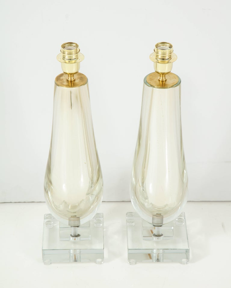 This pair of clear and gold mirrored Murano glass lamps is absolutely stunning! Comprised of handblown clear glass layered over shimmering gold mercury glass to create a mirrored effect. The jeweled base sits atop two solid Murano clear glass square