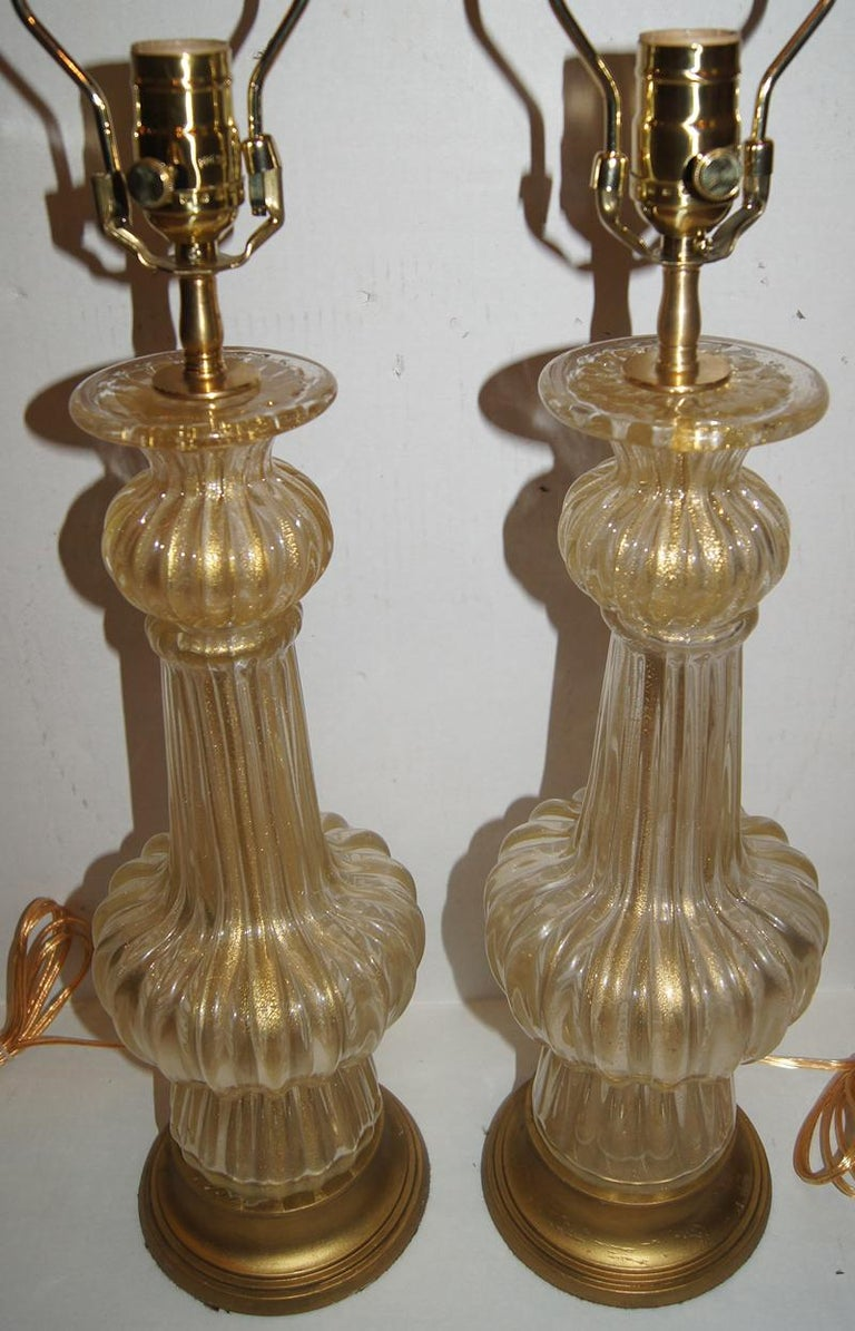 Pair of 1940s Murano clear and gold Murano table lamps with gilt bases.