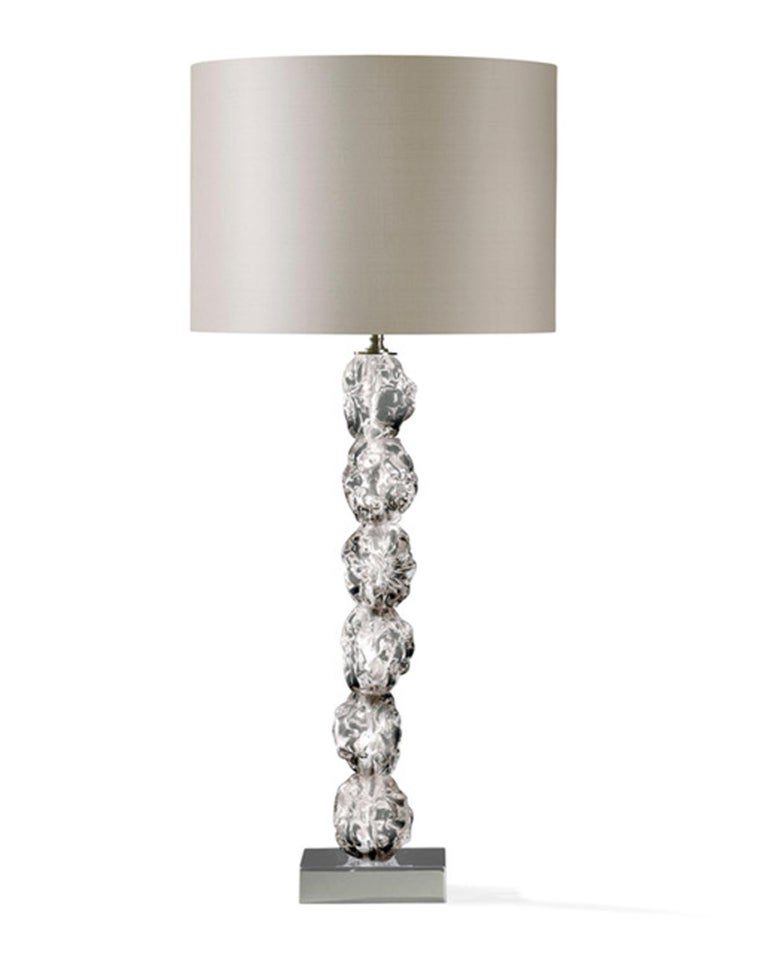 This is a very glamourous table lamp, for its dimensions and for the crystal glass details made as raw pieces, that are very surprising and charming. The raw crystal glass is put in contrast with the elgance of the silk lampshade; the pair it is a