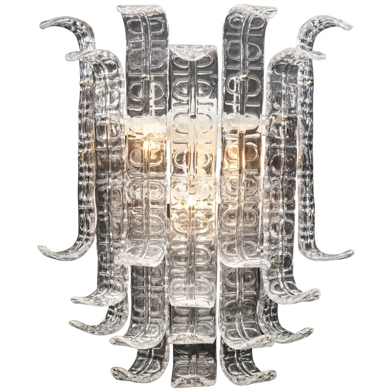 A stunningly large pair of Barovier & Toso style Murano glass sconces consisting of graduating tiers of individually handcasted textured glass elements which delicately curl at the ends, forming a flower like structure. Polished chrome frame.