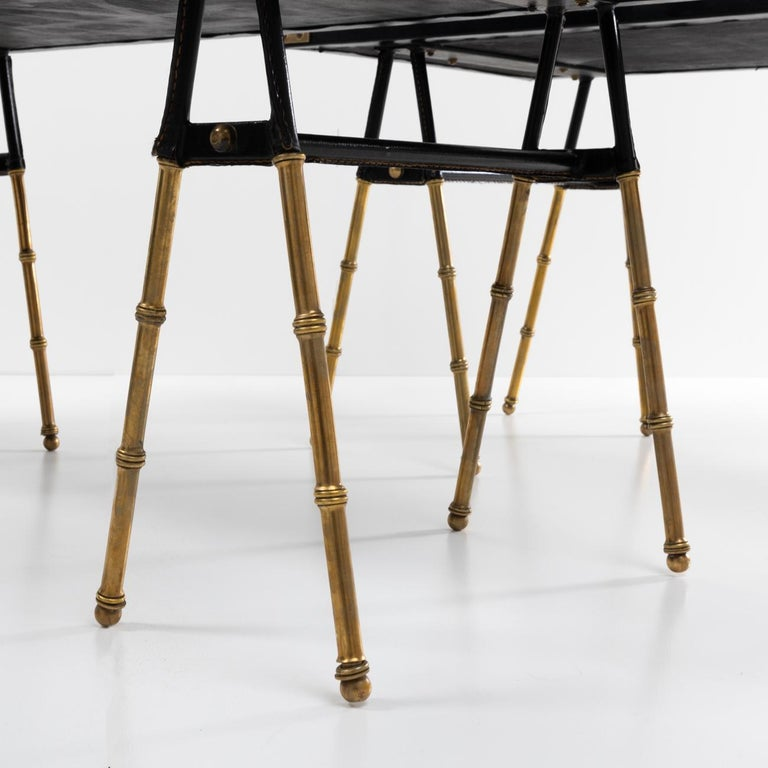 Nice pair of cocktail tables or end tables in solid copper with faux bamboo decor, the upper part covered with saddle stitching leather.  The legs are surmounted by a leather tabletop and decorated with accessories.  The tables are entirely made