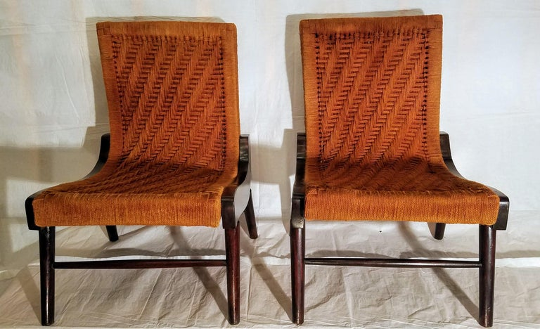 Pair of rare cocobolo rosewood South American lounge chairs wrapped in hemp cord in a herringbone pattern. The chairs were brought back to Virginia by an OSS officer stationed in Central America during World War II. The seats have been rewrapped