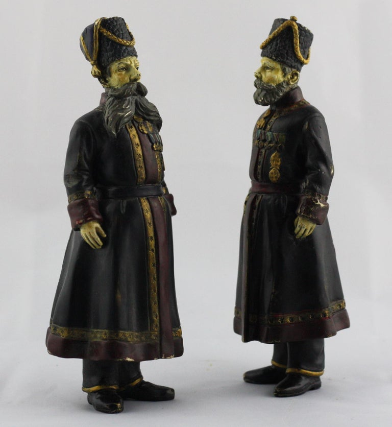 A pair of cold painted bronze figures of the Kamer-Kazaks (Chamber-Cossacks) Pustynnikov and Kudinov.  Accurately modelled and decorated after the original hardstone figures by Fabergé. These faithful copies, each with inscriptions and dates to