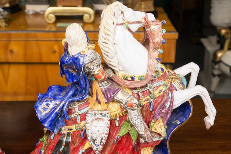 This is a delightful pair of brightly colored Italian glazed porcelain figures depicting elegantly attired knights riding prancing steeds wearing elegant brightly colored saddle draperies. 20th century.