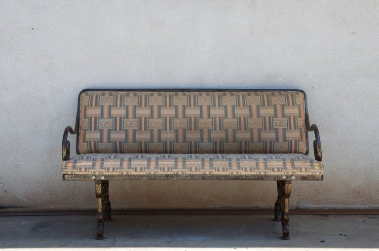 Pair of comfortable French Art Nouveau industrial benches. Also sold individually. Heavy and sturdy wrought iron base. Great for dining. Would need to be reupholstered with C. O. M.