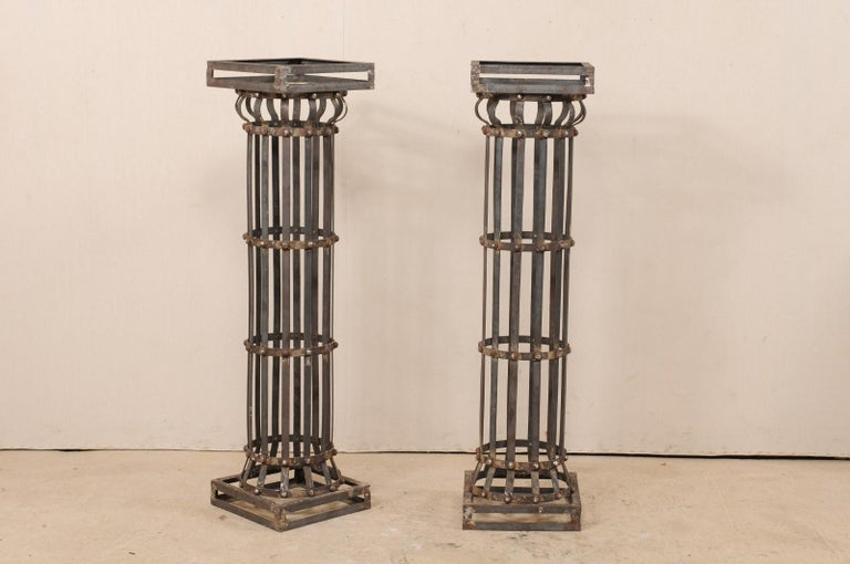 A pair of contemporary American iron architectural columns. This pair of vintage columns feature a round shaped shaft, comprised of vertically set iron strips, with a square-shaped capital and base, and stand at approximately 4.25 feet in height.