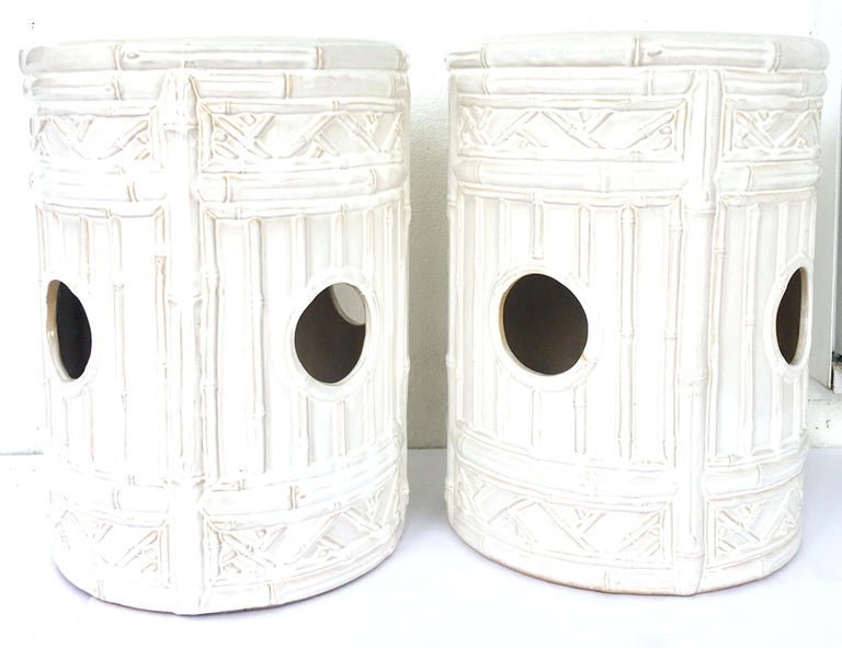 21st Century & New pair of ceramic glaze faux bamboo garden stools. These Hollywood Regency style garden stools are executed in off-white with camel tone detail and each feature cut-out handle detail. Signed on the underside, emissary made in China.