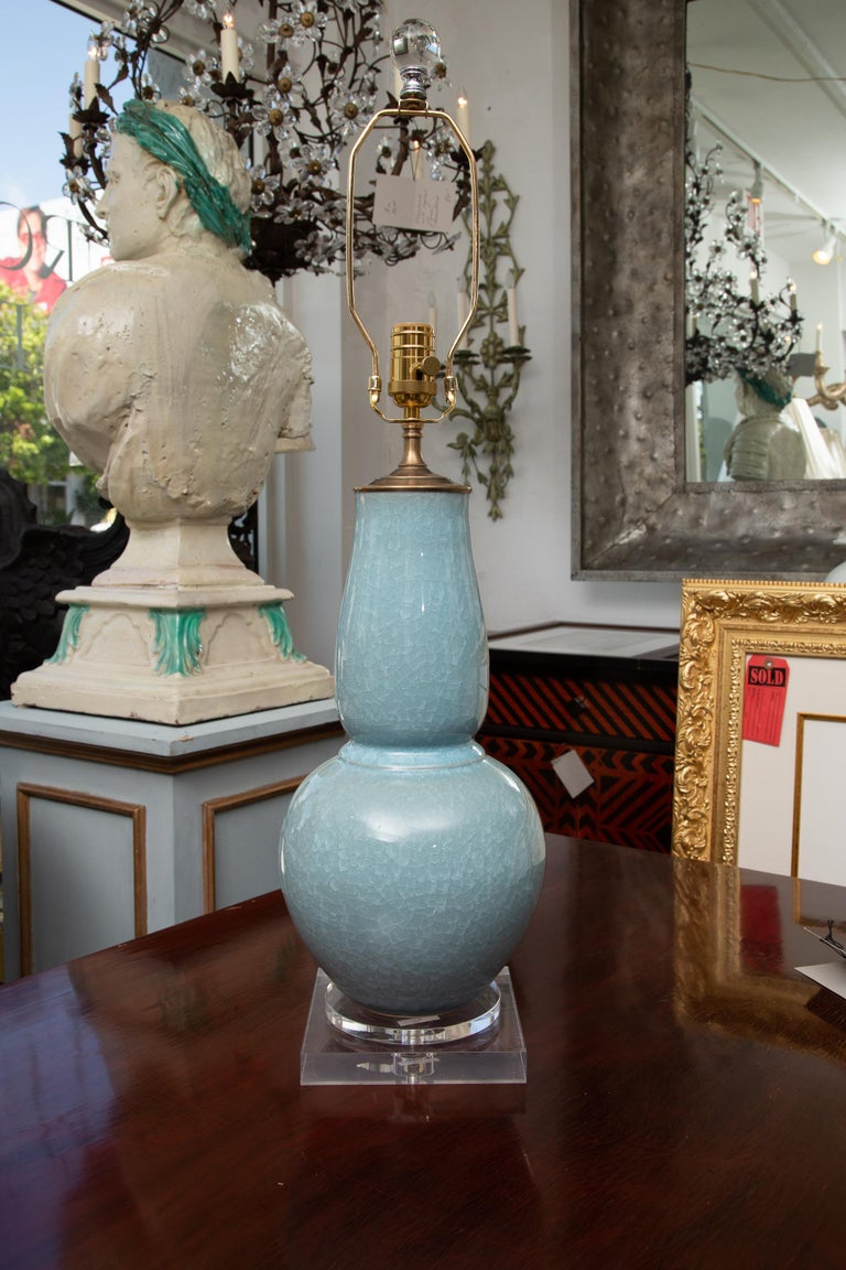 This is a lovely pair of Chinese dark crackled celadon vases converted to table lamps, situated on a square plexiglass base. 20th century.