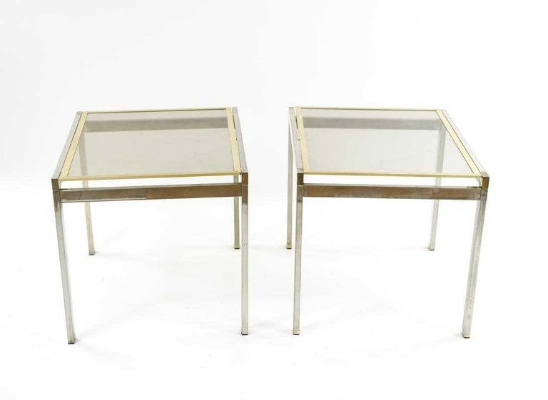The pair of contemporary end or side tables are composed of chrome frames and legs, and glass tops framed in brass that are inset into the chrome frames. The glass and brass tops are removable.