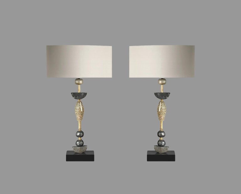 These contemporary Margit Wittig table lamps are mounted on a solid slate bases and feature speckled mouth blown glass shapes in muted grey and brown colours with multiple resin hand-cast spheres and semi-circles which are separated by two brass