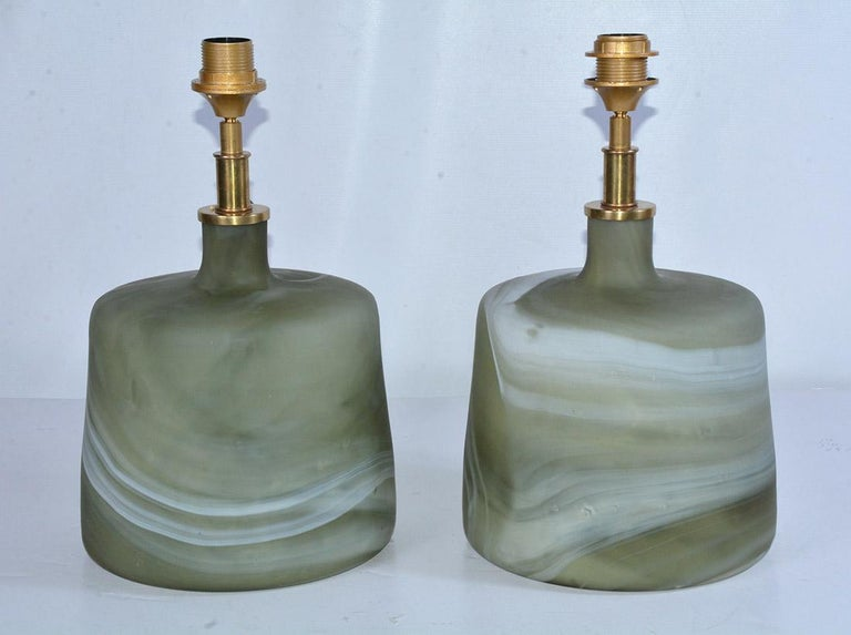 The pair of contemporary one of a kind Murano style green glass lamps have marbleized swirls with mat finish. The designs are not identical. The fixtures are made for European shades. We can change out for you. Cord switch.