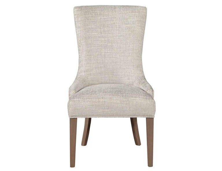 Pair of contemporary high back accent chairs. Designed with a deep seat and concave ergonomic back. Featured in a textured contemporary fabric with satin natural brown legs.  Price includes complimentary scheduled curb side delivery service to the