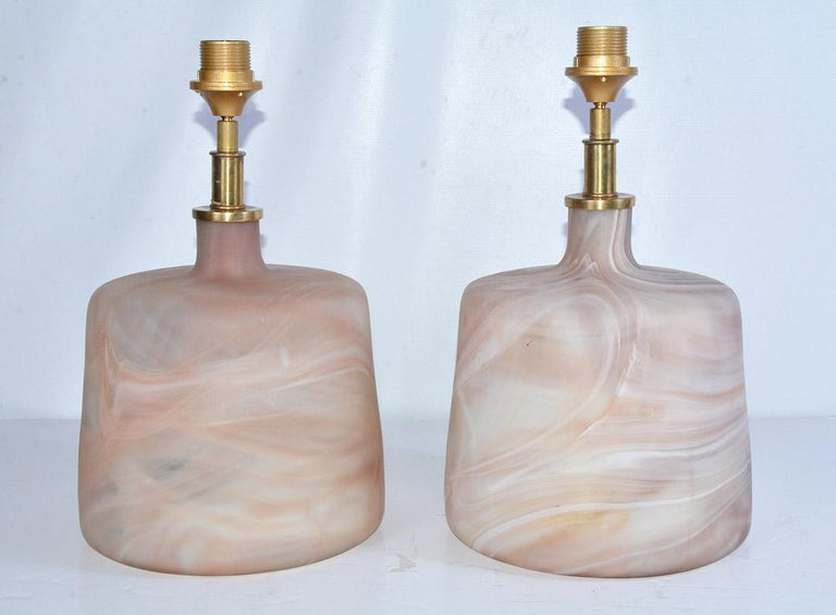 The pair of contemporary one of a kind Murano style glass lamps have marbleized swirls with mat finish. The designs are not identical. The fixtures are made for European shades. We can change out for you. Cord switch.
