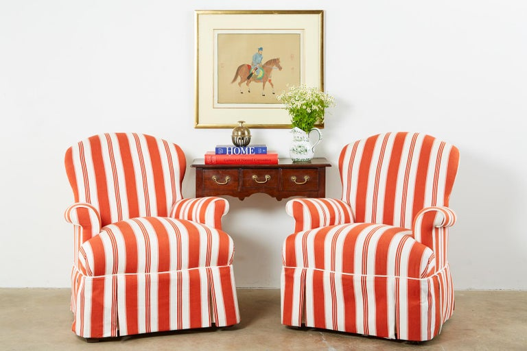 Whimsical pair of upholstered lounge chairs or club chairs featuring a striped fabric. Contemporary style with a hardwood frame. The generous seat has English style flared or rolled arms and is skirted. Like new with excellent joinery and