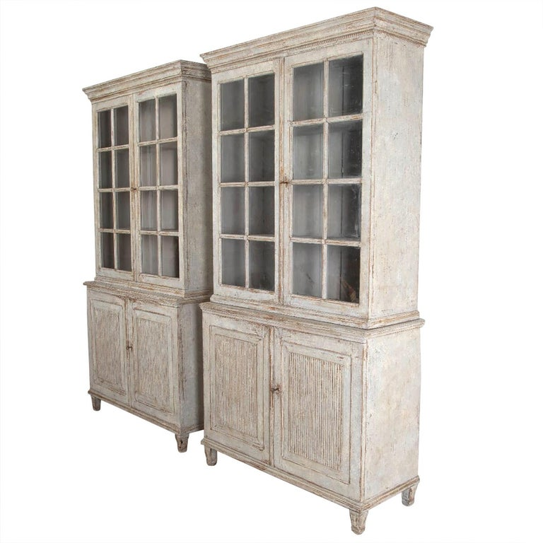 An exceptional pair of continental painted bookcases. Carved cornice with beading edge, with a pair of eight glazed paneled doors opening to storage shelves. Two further reeded doors open to further storage. These bookcases have tapered legs, 20th