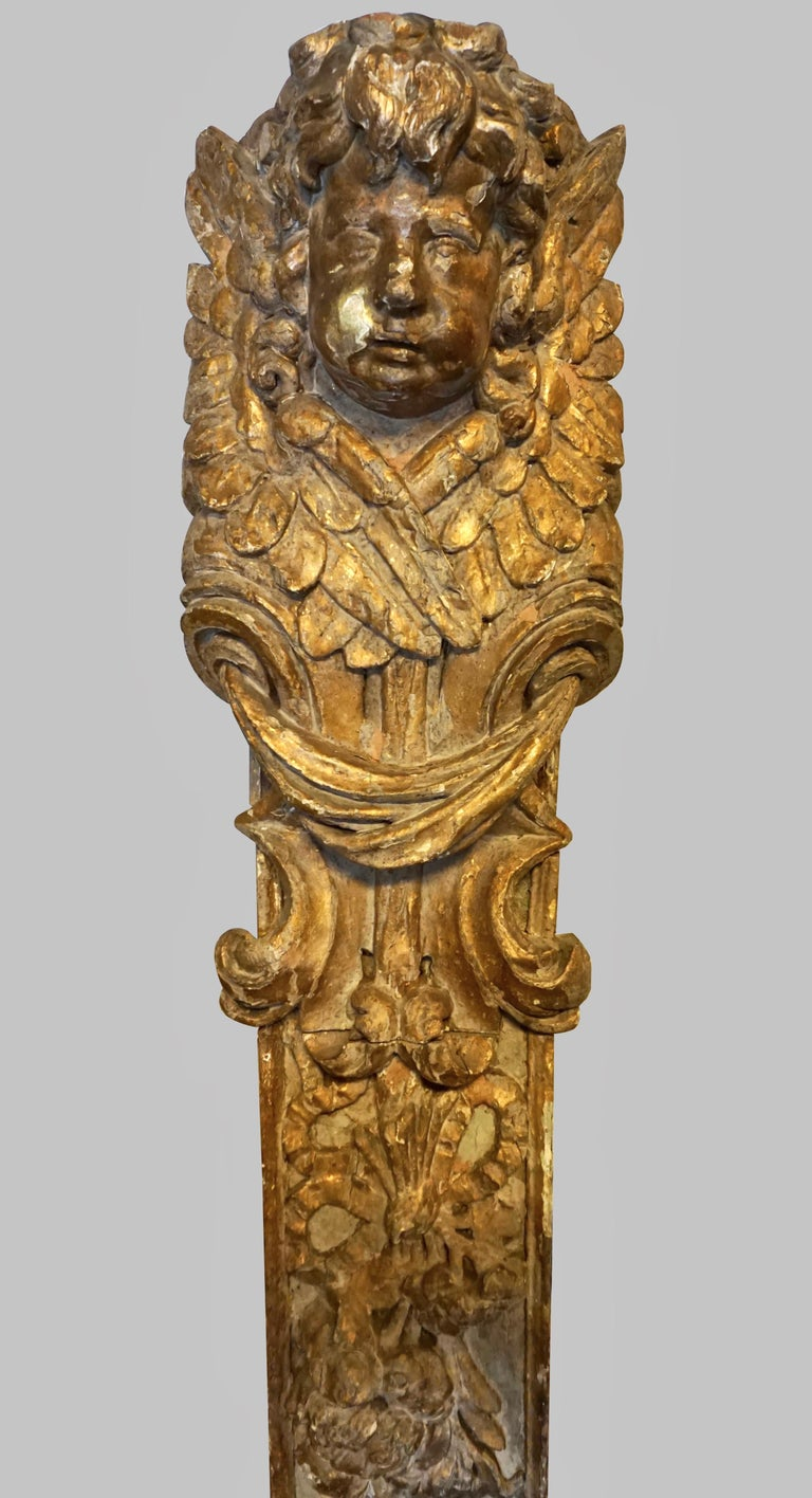 A dramatic pair of parcel gilt and painted architectural fragments of substantial scale, each well-carved element topped by the head of a putto surrounded by feathers and garlands. Probably Italian, 18th century or earlier. Substantial scale with