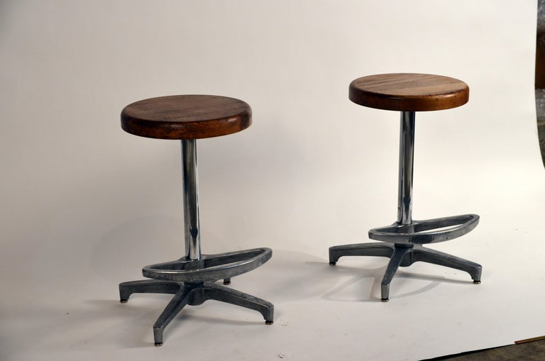 Pair of counter height swiveling bar stools. The footrests swivel as well, or can be locked into position. Great patina to the metal bases and the wood seats.
