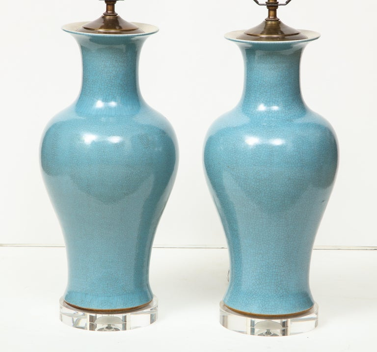 A stunning pair of Chinese ceramic lamps in a soft blue on a Lucite base.