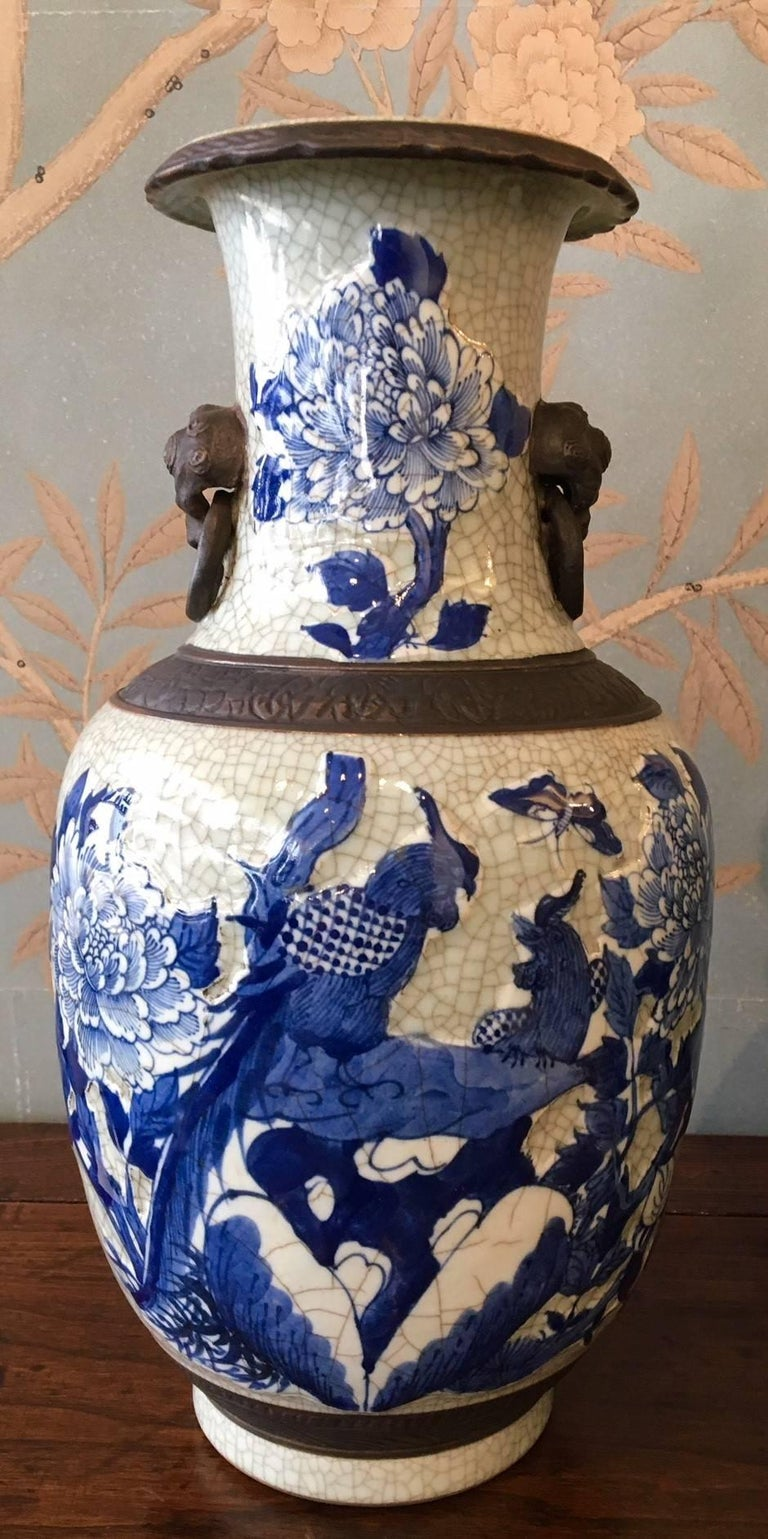 A pair of early 20th century blue and white crackleware vases with faux bronze bands, birds, butterflies and flowers.