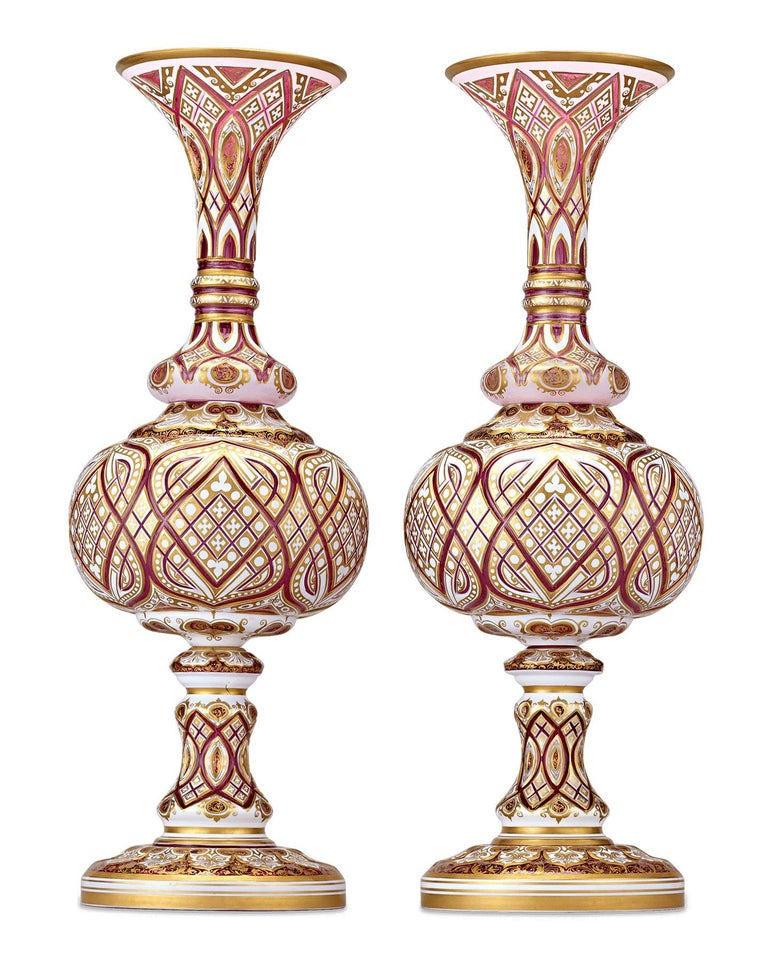 This resplendent pair of art glass vases exhibit the incredible detail and craftsmanship exemplary of Bohemian art glass. Rare crimson glass — the most coveted of Bohemian glass hues — mingles elegantly with white and gold in an intricately