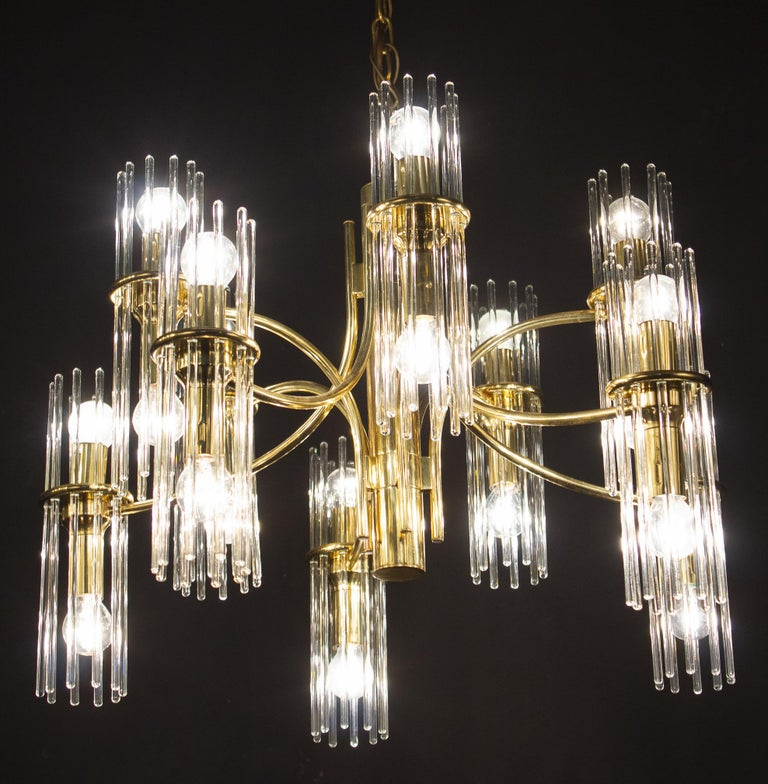 Pair of midcentury Gaetano Sciolari clears glass rod modernist chandeliers with brass frame.