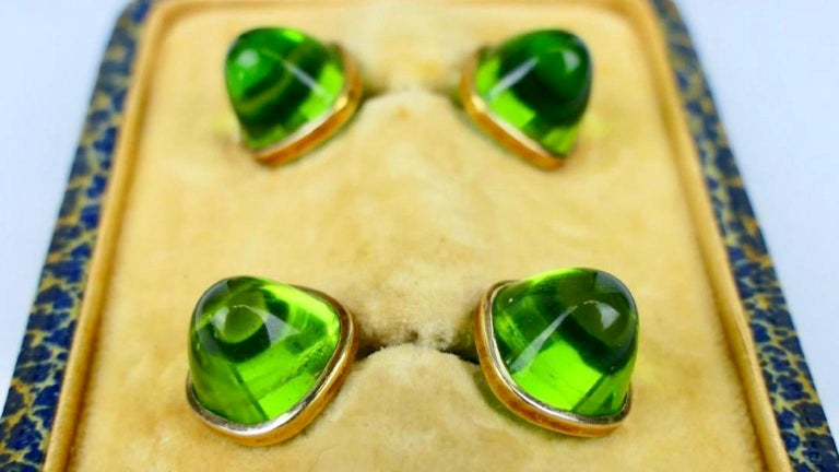 A pair of midcentury cufflinks crafted of 18-karat yellow gold and featuring high dome bullet shaped gum drop cut green glass Moldavite stones in a fitted presentation box from Le Palais Royal Joyeria, Habana Cuba. Cufflinks measure approximately 1
