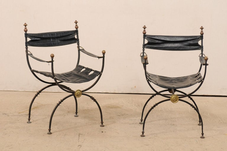 A pair of Italian curule Savonarola chairs with black leather from the early 20th century. This pair of antique Italian curule chairs, also commonly called Savonarola, which are defined by their signature semi-circular frames which connect where the