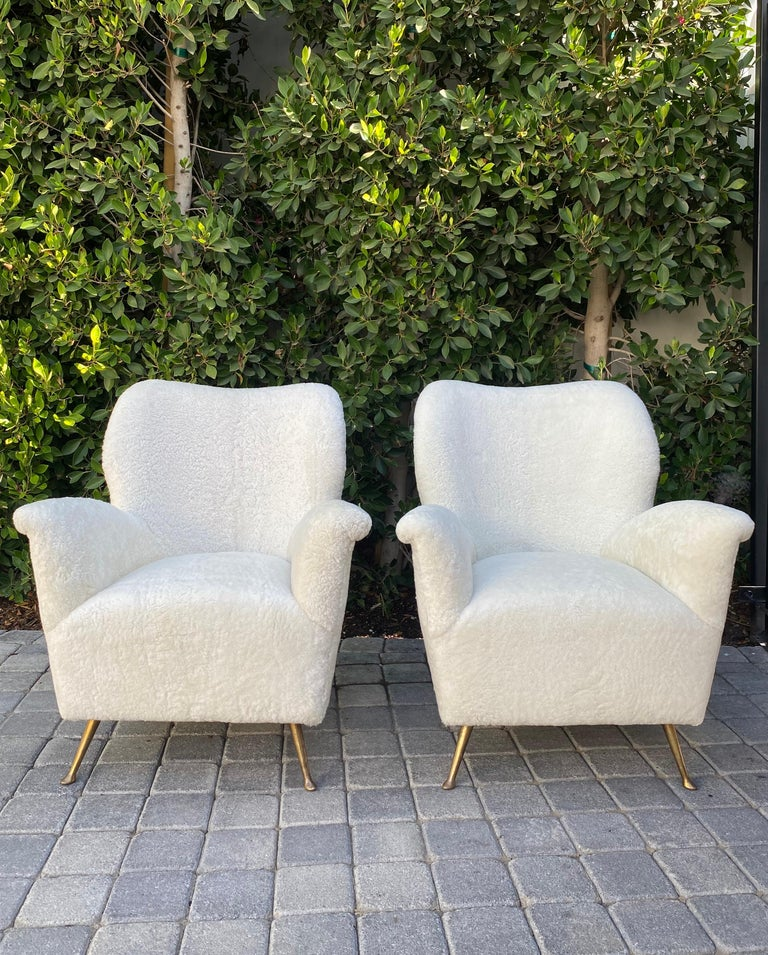 Pair of curved midcentury lounge chairs in white curly shearling reimagined from original Isa Bergamo form with solid brass legs.