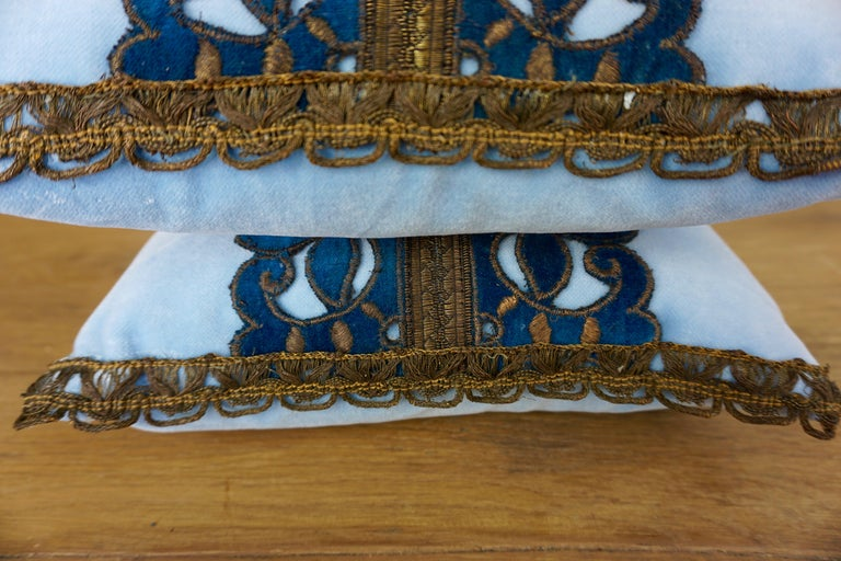 Pair of custom accent pillows designed by Melissa Levinson Antiques. The pillows are made with 19th century metallic and velvet appliqués on sky blue velvet fronts and backs. Down inserts, zipper closures.