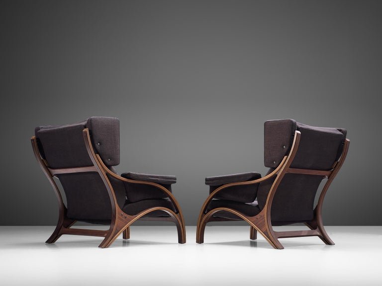Giampiero Vitelli, pair of lounge chairs to be reupholstered, rosewood and fabric, Italy, 1960s.  Set of Italian wingback chairs that feature curves and gracious forms. The most interesting feature is the rosewood frame with its fluid lines. The
