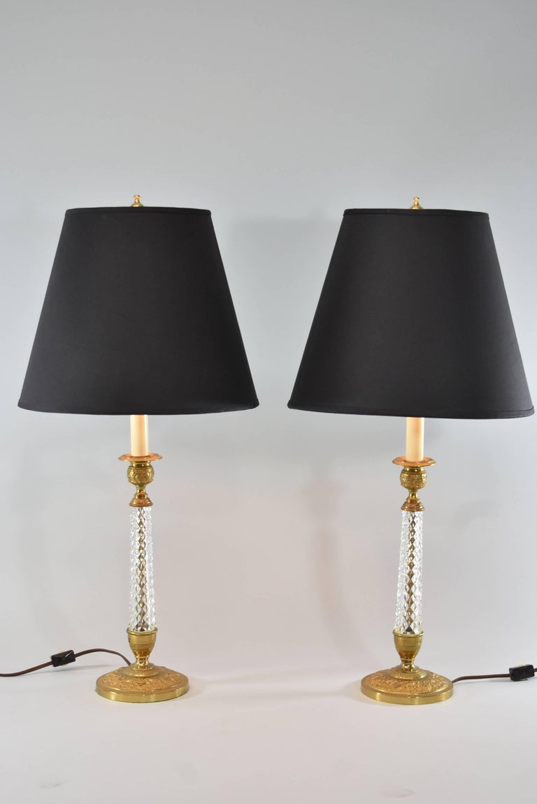 A stunning pair of boudoir lamps. They feature a gold doré finish with grapes and vines and beautiful cut-glass in a candlestick form. They each have a single socket. The shades are not included.