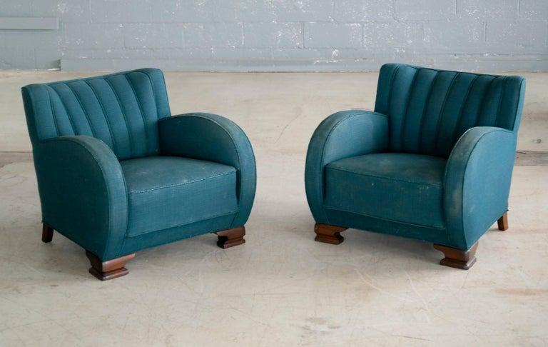 Exuberant, curvy and very eye-catching pair of Danish club chairs from the 1930s. Set on block feet typical of the period and with a channeled back reminiscent of sports car seats of the era. Sturdy and sound construction but with significant wear