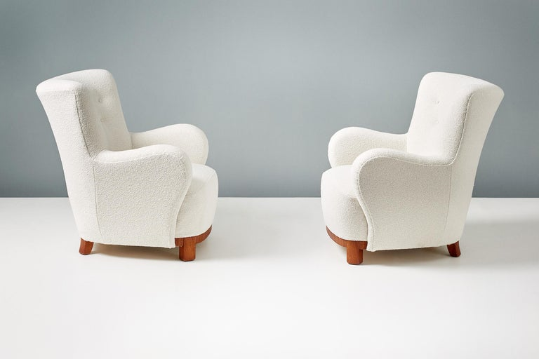 A pair of Danish cabinetmaker 1950s lounge chairs reupholstered in luxurious cotton-wool blend off-white bouclé fabric from Chase Erwin in England. The legs and based are made of African Mahogany.   Each chair has been fully reconditioned in our