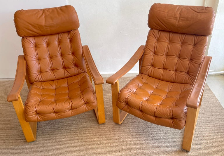 Pair of Danish cognac leather club chairs, circa 1960s  Made in Finland by OY BJ. Dahlqvist for Hounekalutehads-Mobelfabrik. The leather tufted leather backrest and seats and armrest, supported by bentwood frames. Each chair measures 38