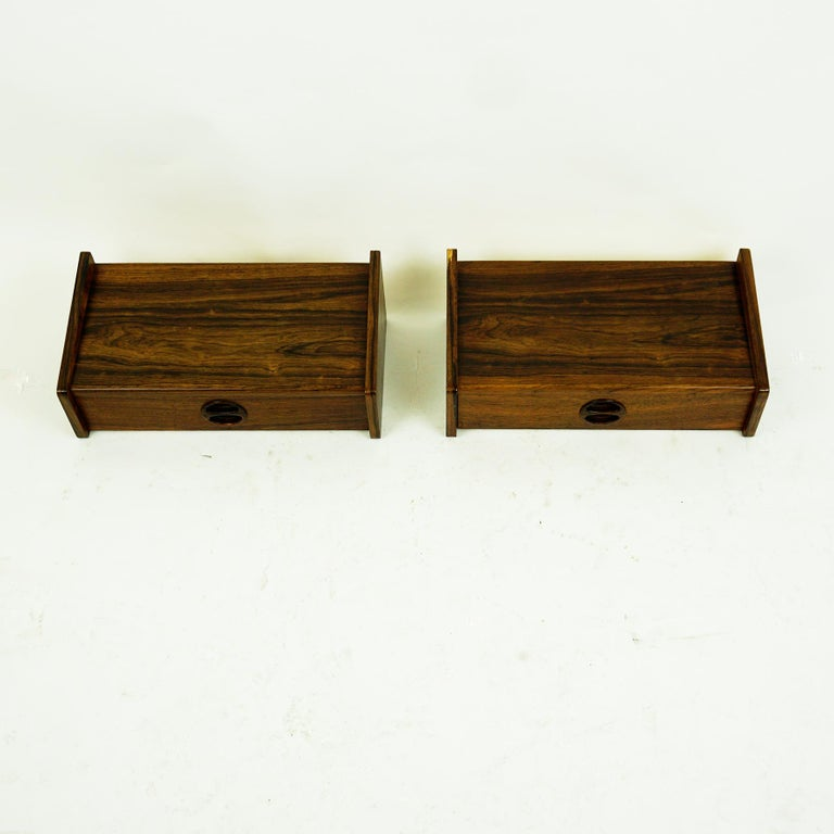 Charming small floating Danish rosewood nightstands ore shelves from the 1950s with a simple streamline design, featuring one drawer each. They can be used as a nightstand or as well in the wardrobe. Authentic example for Danish modern design from