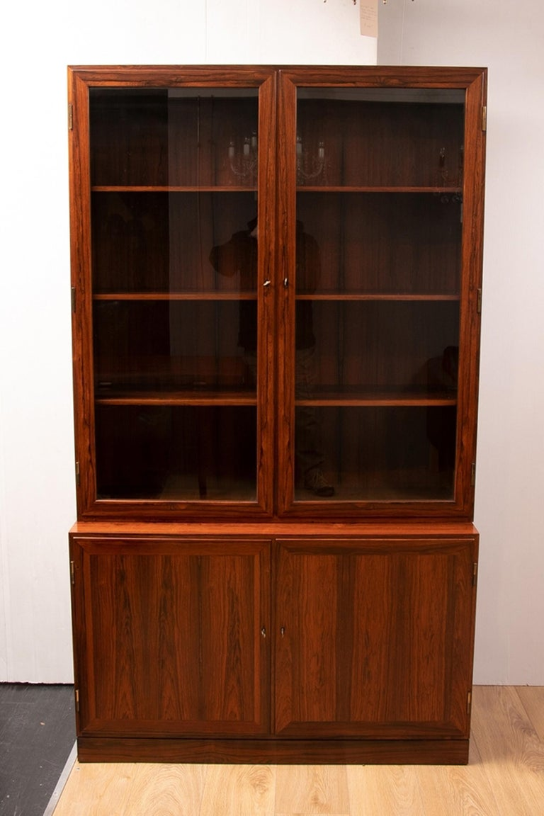 Kai Winding rosewood Alcove bookcases, circa 1970 A rare pair of Danish midcentury rosewood bookcases one glass-fronted and the other doored designed by Kai Winding. Re polished and in perfect condition-home ready. The tops are  H-48 1/2
