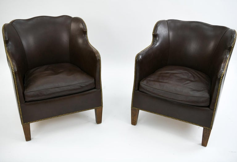 This is a handsome pair of Danish library chairs. Upholstered in leather, these chairs feature brass tacked edges and scalloped backrests. These chairs would be attractive in both modern or traditional interiors for their timeless appearance.