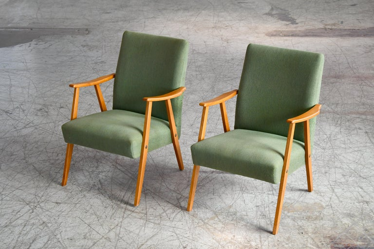 Really nice pair of 1960s easy chairs very similar in style to some of Arne Vodder's typical designs with the slight curvature to the armrests in solid elm wood and the slightly higher backrest. Nice light versatile chairs and overall in very good