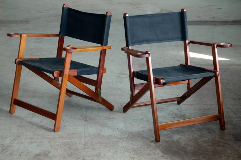 Unique and very charming folding deck chairs made in Denmark in the 1950s. Built in cup holders in armrests and one chair has a brass coaster. Very comfortable and sturdy made from solid teak on brass hinges with seat and backrest in black canvas.