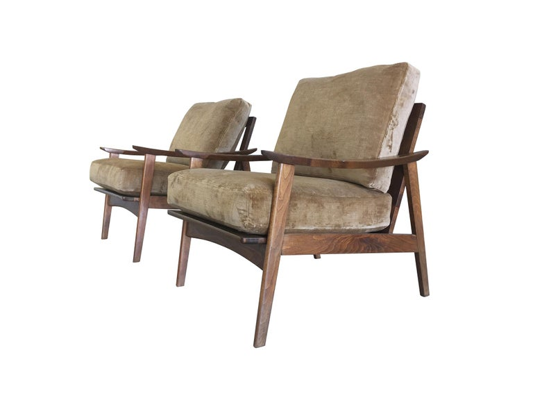 A pair of handsome lounge armchairs handmade in Denmark, mid-20th century. Their frames are maple wood crafted in a sleek, minimal design. Smooth, beautifully rounded edges characterize their modern style, as do the slanted legs that give the frame