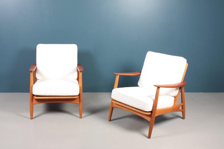 Pair of lounge chairs in teak, oak and upholstered with new bouclé. Designed by Johannes Andersen and made by Københavns Møbelfabrik A/S in 1960s. Great condition.