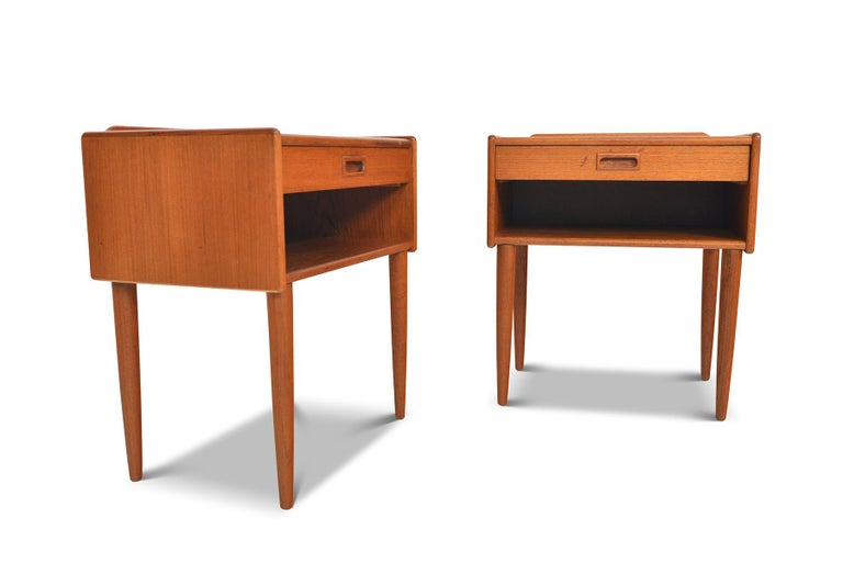 This handsome pair of Danish modern midcentury nightstands blend form and function seamlessly. A single pullout drawer provides storage for smaller items with a roomy open cubby beneath. In excellent original condition with typical wear for their