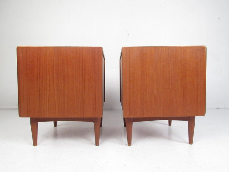 This stunning pair of Mid-Century Modern nightstands feature a large compartment with a drawer hidden by a tambour door. An unusual par of side tables with tambour doors that function vertically rather than horizontally. A sleek design with