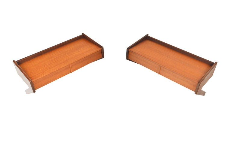This pair of Danish modern floating wall nightstands was produced by Olholm Møbelfabrik. Crafted in teak with contrasting details in teak afrormosia, two drawers offer storage. In excellent original condition with typical wear for its vintage.