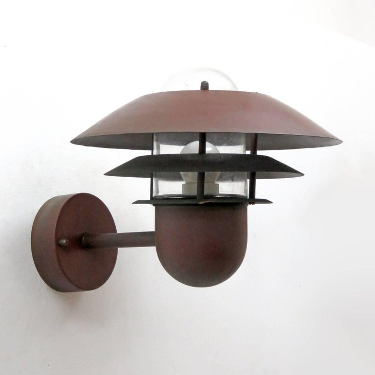 Great pair of Danish outdoor wall sconces by Nordlux in copper with glass bulb enclosures.