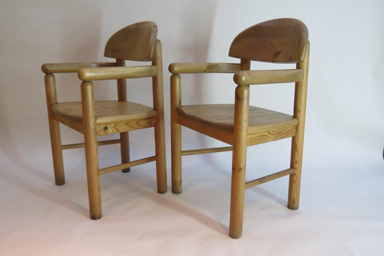 Pair of Carver dining chairs made from solid pine, designed by Rainer Daumiller, and manufactured by Hirtshals Sawmill in Denmark, circa 1970s.  Very well made solid carver chairs in good over all condition, some signs of wear to arms as shown in