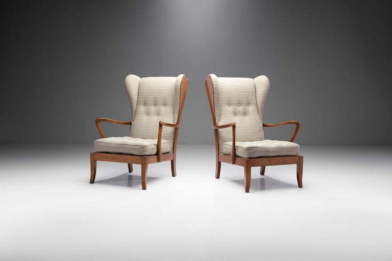 """This pair of Danish cabinetmaker chairs, often referred to as """"Øreklapstolen"""" or """"ear flap chairs"""" is a great example of the Danish Mid-Century Modern aesthetic.  Danish design is torn between epochs; it is a term that accommodates both the"""