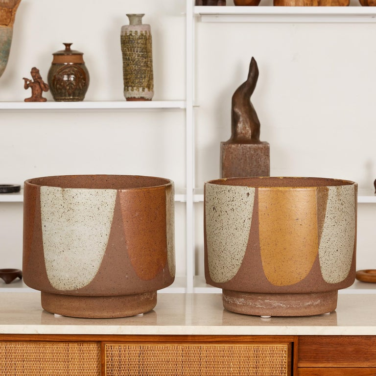 "A pair of planters by Architectural Pottery with David Cressey's Pro/Artisan ""Flame Glaze."" The stoneware planters feature a round form with flat foot, a simple shape rendered dramatic by the white, brown, and orange painterly glaze that mimics"