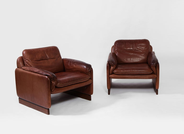 Pair of De Sede lounge chairs in original cognac leather enriched with a deep patina and saddle stitch detail. Each leg rests on a linear walnut bases. Iconic 1970s Italian furniture.