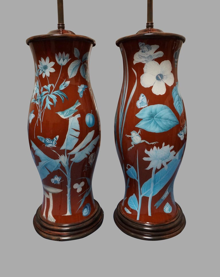 A highly decorative pair of decalcomania baluster form lamps decorated overall with exotic birds, frogs butterflies and plants in colors of red, orange, green and blue mounted with wooden bases and caps. Wonderful design and substantial scale. No